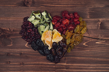 Heart of dried fruits closeup on brown wooden background. Decorative composition for Valentine's Day. Top view.
