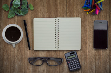 Office desk table with computer, supplies, coffee cup and flower on wood background.Top view with copy space.