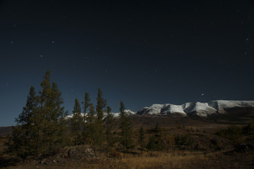 Soft magical moonlight with stars over snowy mountains of Altai