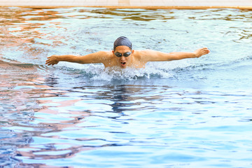 dynamic and swimmer in cap breathing performing the butterfly st