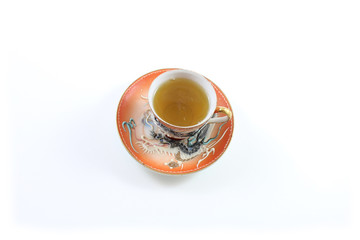 Top view of orange and white Japanese dragon teacup and saucer with tea, isolated on white