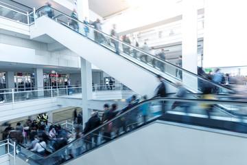 Blurred people using a escalator on a European Trade Fair