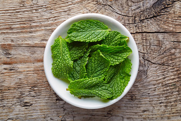 Bowl of mint leaves on wooden table, from above