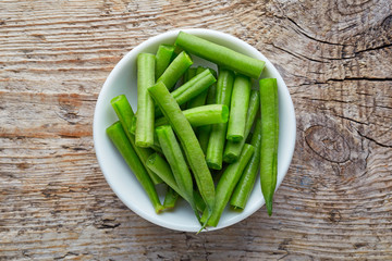 Bowl of green beans on wooden table, from above