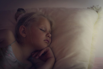 Beautiful little girl is sleeping. Dreamy colorized and soft focus photo.