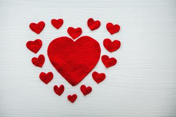 Красные сердца из фетра разного размера на белом деревянном столе.