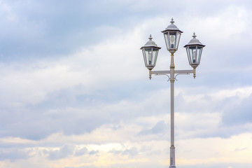 Old street lamp on a background of cloudy sky. Soft colors. Beautiful background.