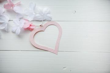 нежное розовое сердце из бумаги с белыми и розовыми цветами на белом деревянном столе ко дню святого валентина