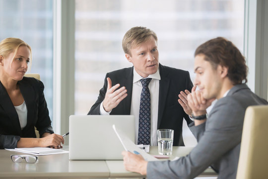 Furious boss scolding young frustrated intern with bad work results. Ineffective office worker receiving a dismiss notification sitting at the table, listen to irritated boss yelling
