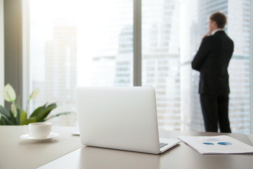 Company president in formal suit standing, looking through window at cityscape, dreaming, planning new projects, resting after intensive work. Focus on laptop on office table. Business success concept