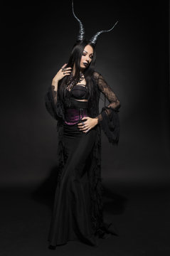 Young woman in black fantasy costume with big horns on dark background