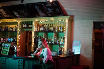 Waitress sitting at counter in bar
