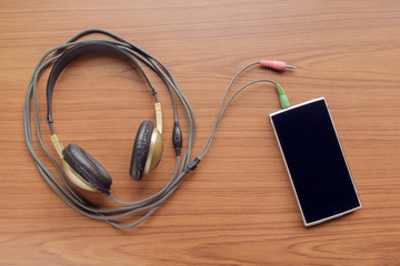 Headphone and smart phone / View of headphone and smartphone on wood table. Top view.
