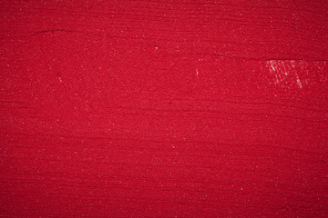 Close up plane background texture of solid red color made of soil.