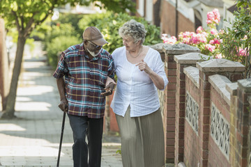 elderly inter racial couple help each other walk up a hill