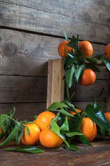 Tangerines with leaves on wooden box over old wooden table. Dark rustic style.