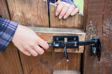 Young woman opening lock on wooden door