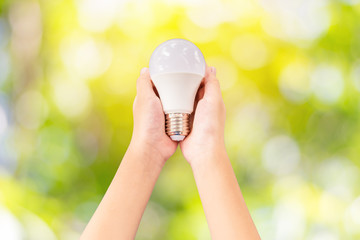 Closeup LED lighting bulb in hands with the colorful green nature background, Concept for energy saving.