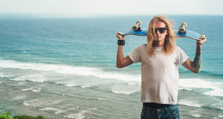 Portrait of Young man blonde in sunglasses skater standing with skateboard on the mountain  in front of amazing sea view