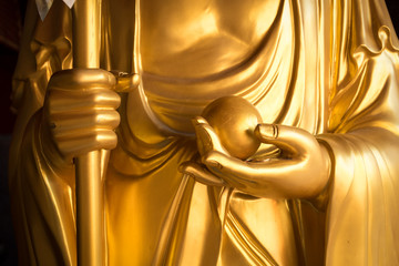 close up golden monk hand with golden ball image of buddha means