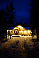 Winter Cabin Glowing Warm at Night Blue Sky