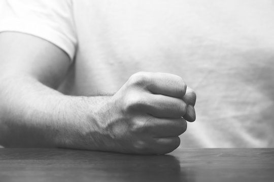 Man is hitting his fist on the table. Image in black and white.