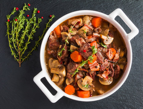 Beef Bourguignon in a casserole on black stone. Stewed with bacon, garlic, carrots, onions, mushrooms,  red wine, fresh thyme and spices. Top view.