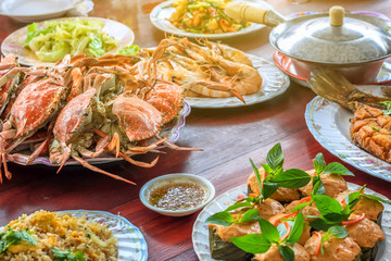 Thai style set of seafood insist of Thai steamed curry fish in banana leaf cups decorated with basil leaf, (Hor Mok Pla) steamed crab/prawn/shrimp with seafood sauce