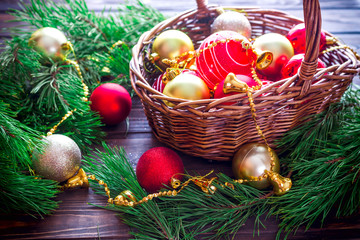 Christmas magic composition with pine cone,  bells and red and gold balls in the basket on dark wooden vintage background. Beautiful holiday decoration