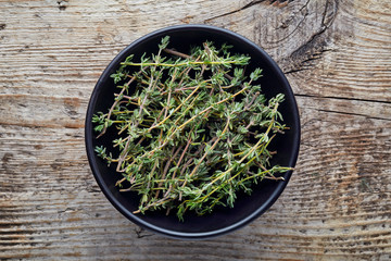Bowl of thyme on wooden table, from above