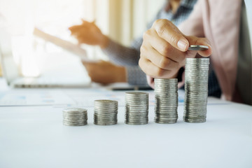Saving money concept. Close-up Of Businesswoman Hand Put Coins To Stack Of Coins