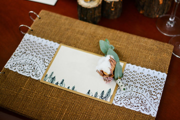 Wedding decor photo album with rings and twig cotton.