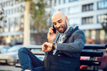Businessman talking on the phone and looking at watch