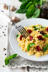 Bulgur with dried tomatoes and basil on a light wooden background. Vegetarian dish. Selective focus.