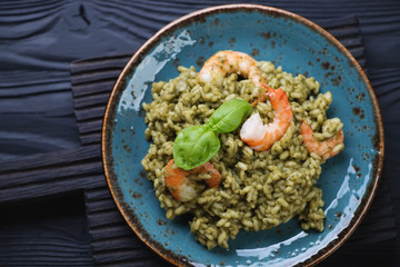 Risotto with spinach and tiger shrimps on a black wooden surface