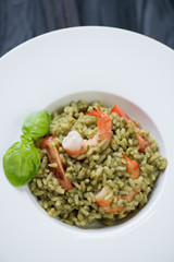Closeup of spinach risotto with tomatoes and tiger shrimps