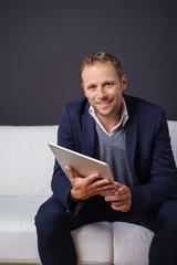 geschäftsmann sitzt auf einem weißen sofa und hält ein tablet in der hand