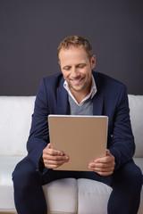 mann schaut lächelnd auf tablet-pc