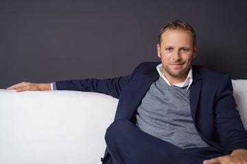 mann sitzt lässig auf einem weißen sofa
