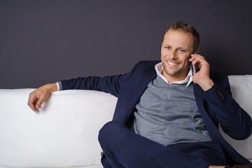 mann sitzt auf einem sofa und telefoniert