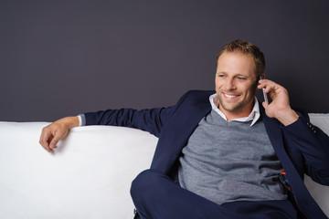 geschäftsmann sitzt entspannt auf einem sofa und telefoniert