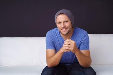 lächelnder mann sitzt auf einem weißen sofa