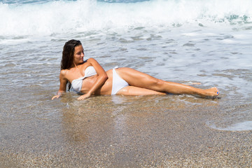 Beautiful tanned brunette in white bikini lying on the beach