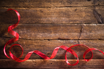 Decorative red ribbon on the wooden background