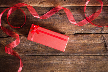 Decorative red ribbon and gift box on the wooden background
