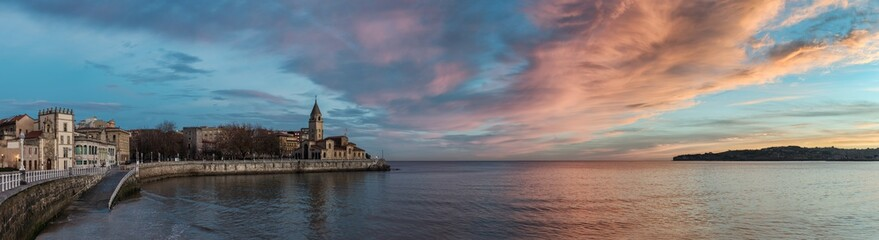 San Pedro church in San Lorenzo beach in Gijon in Asturias natural paradise travel touristic destination for vacations in Spain at dawn before sunrise. Panorama with calm sea landscape background.