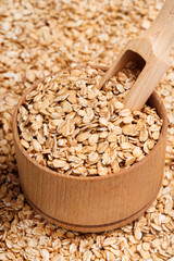Close up oats in wooden bowl and scoop. Healthy food. Top view, high resolution product.