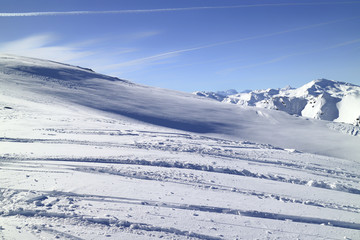 Winter landscape in high Alps with shimmering fresh snow, rugged peaks in the distance. Blue sky  with contrails.