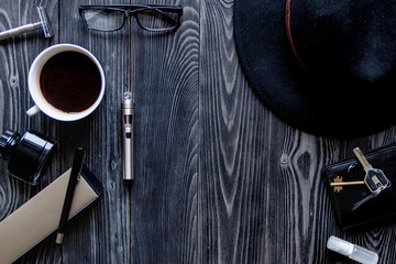 coffee, electronic cigarette, mens accessories dark wooden background top view