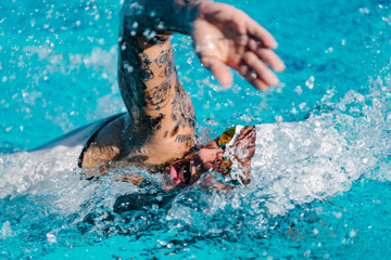 front crawl swimmer. Female front crawl swimmer with tattoos